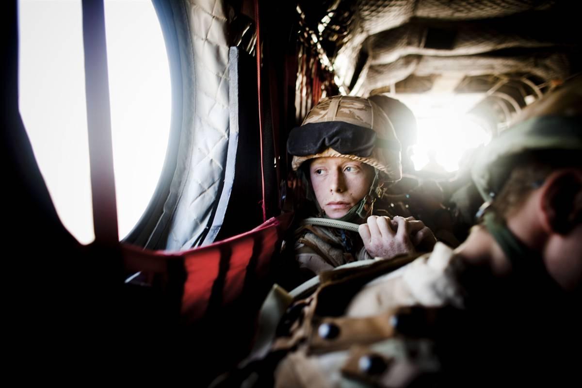 """2) Британские военные из 1-го батальона валлийской гвардии летят на вертолете к операционной базе в афганской провинции Гильменд 24 июня. Афганские и коалиционные силы пытаются снова взять под свой контроль сельскую местности в таких районах, как Гильменд и Кандагар, которые сейчас контролируются движением """"Талибан"""". (Eros Hoagland/The New York Times via Redux Pictures)"""