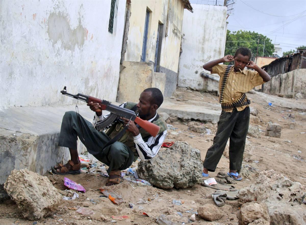 4) Мальчик с боеприпасами стоит рядом с исламистом, который стреляет по военным сомалийской правительственной армии во время столкновений 3 июля в столице страны Могадишо. За последние два месяца правительство сомалийского президента шейх Шарифа Шейх Ахмеда подверглось усиленным атакам со стороны исламских мятежников. (Mohamed Sheikh Nor/AP)