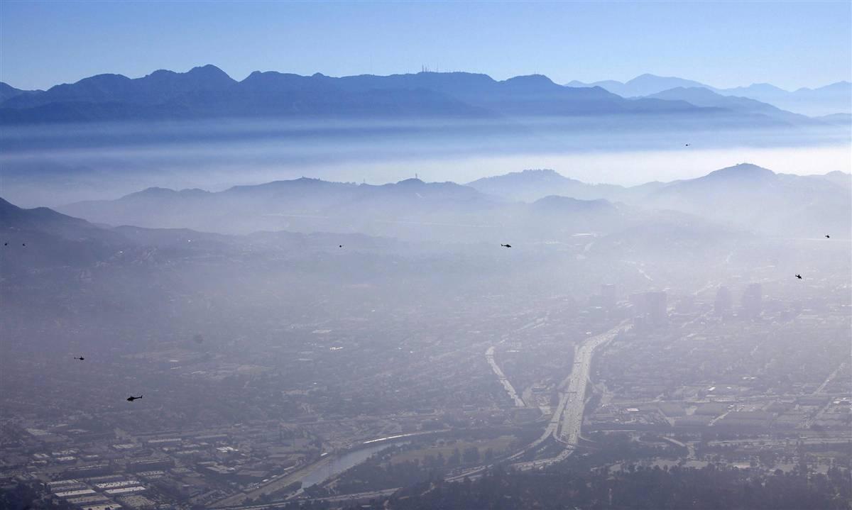 6) Более 20 вертолётов средней грузоподъёмности (на снимке видно девять) летают над мемориальным парком Форест Лон, где 7 июля прошли закрытые похороны поп-звезды Майкла Джексона. (Vincent Laforet/EPA)