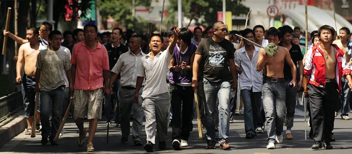 8) Большая группа китайцев народности хань, вооруженных палками, лопатами и другими импровизированным оружием идет вдоль улицы в Урумчи, столице провинции Синьцзян 7 июля. Полиция применила слезоточивый газ для разгона тысяч протестующих, вооруженных самодельным оружием,  после того, как хаос охватил город, расколотый от этнической напряженности. За выходные во время стычек между китайцами хань и уйгурами-мусульманами, по меньшей мере, 156 человек погибли и более 1100 получили ранения. (Peter Parks/AFP - Getty Images)