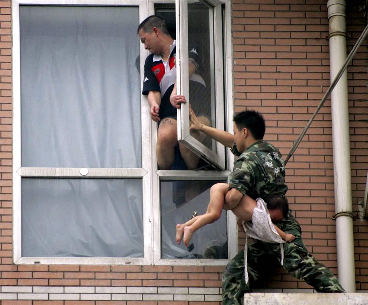 9) Пожарный держит 2-летнюю девочку и пытается закрыть окна, чтобы не дать отцу ребенка выпрыгнуть из окна в городе Чэнду, юго-западной провинции Сычуань. в, на 7 июля. Как сообщает China Daily, находящийся под действием наркотиков мужчина хотел выбросить свою двухлетнюю дочь из окна 8-этажного дома и выпрыгнуть сам. Спасателям удалось отвлечь мужчину и выхватить у него из рук ребенка. (Reuters)