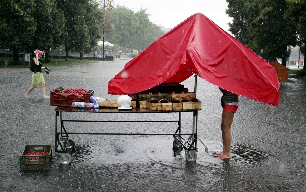10) Торговка клубникой закрывает зонтом свой товар во время проливного дождя в центральном районе Варшавы. Снимок сделан 5 июля. (Tomasz Gzell/EPA)