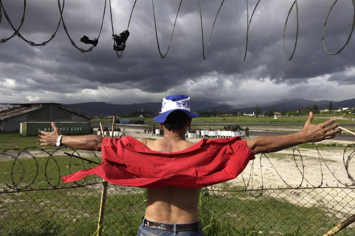 12) Сторонник свергнутого президента Гондураса Мануэля Селайи подставляет свою грудь солдатам после того, как они открыли огонь и убили, по меньшей мере, одного человека, в международном аэропорту в Тегусигальпе 5 июля. Самолету Селайи не дали приземлиться, поскольку взлетно-посадочная полоса была заблокирована военно-транспортными средствами. (Rodrigo Abd/AP)