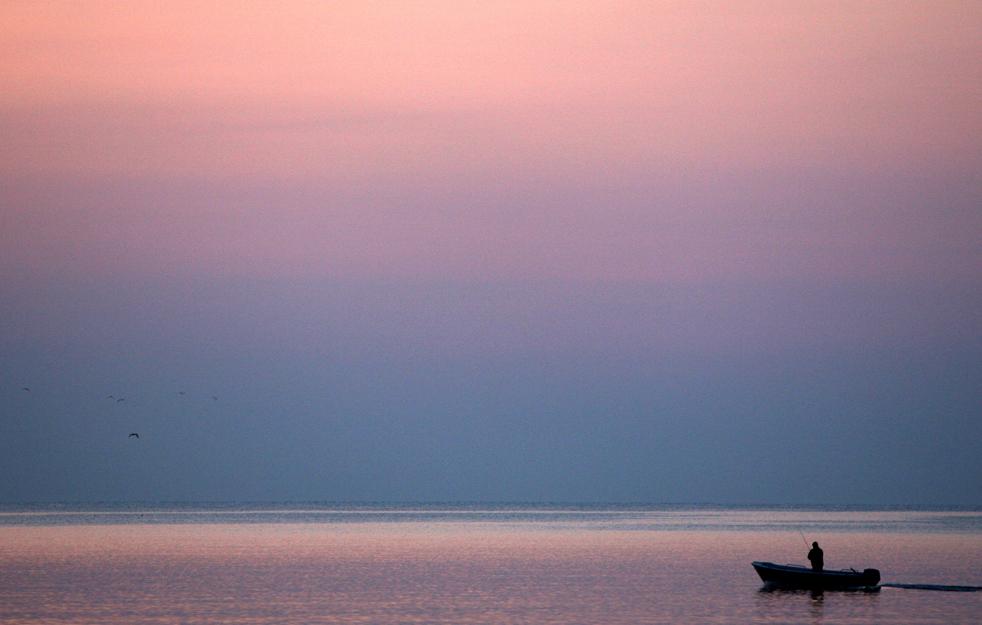 1) Рыбацкая лодка рано утром до восхода солнца у берега Черного моря в районе болгарского города Варна, 9 июля. (AP/Petar Petrov)