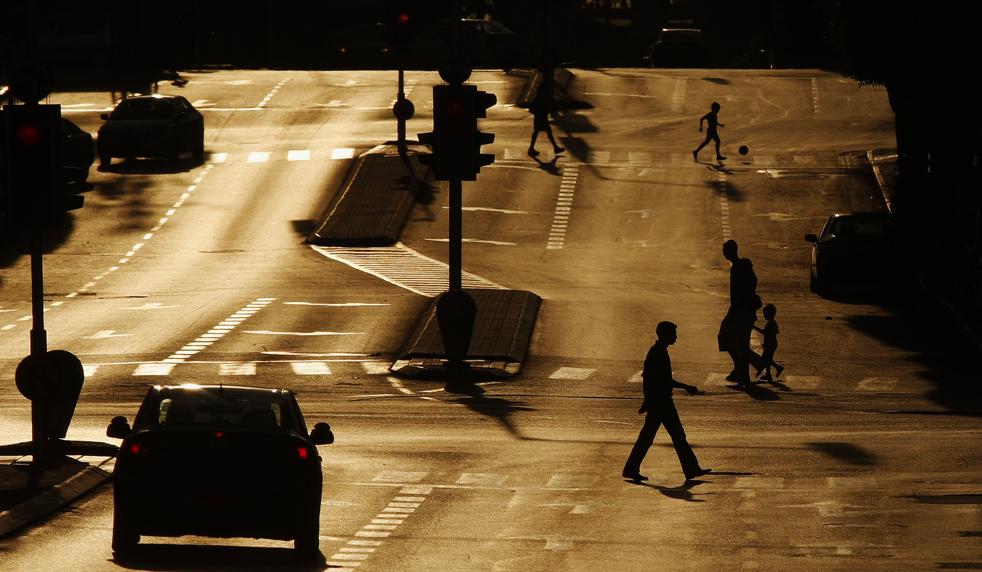 5) Израильтяне пересекают главную улицу израильского приморского города Нетания на закате 3 июля. (AP/Muhammed Muheisen)