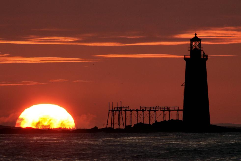 8) После долгого периода пасмурной погоды солнце снова поднимается над маяком Ледж Лайт на острове Рам уступе свет в устье Портленд-Харбор, 9 июля. (AP/Robert F. Bukaty)