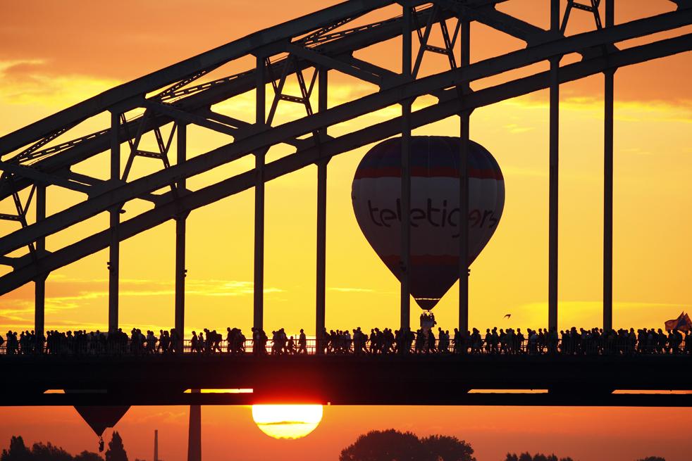 9) Участники 93-го четырехдневного Неймегенского перехода пересекают реку Ваал недалеко от голландского города Неймеген 21 июля. В переходе приняли участие 41205 человек из 64 стран. Участники могут выбрать дистанцию: 30, 40 или 50 километров. (AFP/Getty Images/Vincent Jannink)