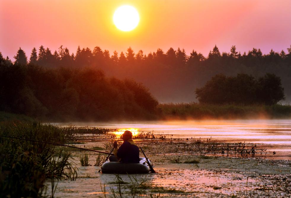 10) Белорус рыбачит с лодки у берега реки в деревне Белино 19 июля. Рыбалка – популярное круглогодичное времяпрепровождение в Беларуси. (AFP/Getty Images/Viktor Drachev)