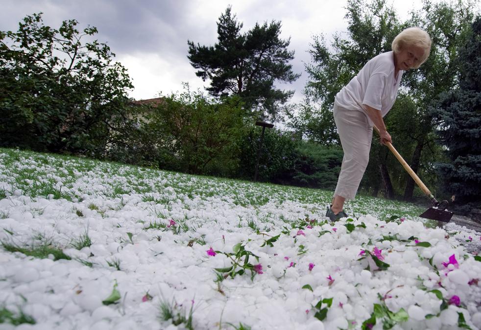 11) Женщина пытается очистить свой сад в Ле Ессер недалеко от Лозанны. Сильный град прошел в западной Швейцарии во второй половине дня 23 июля. (AFP/Getty Images/Fabrice Coffrini)