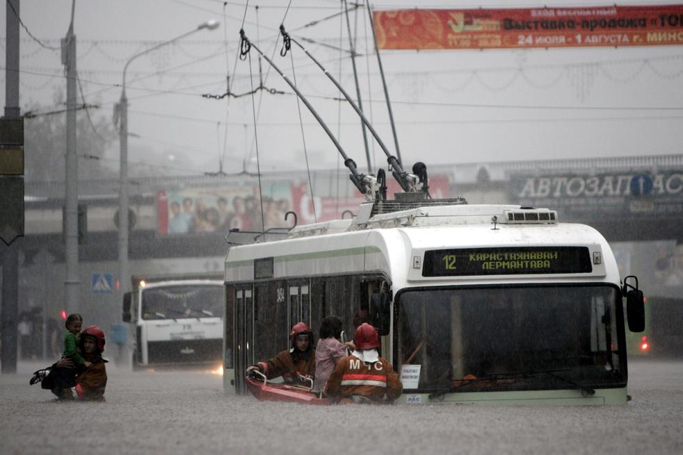 12) Спасатели помогают работникам общественного транспорта выбраться из троллейбуса во время наводнения в центральной части Минска, которое было вызвано сильными дождями. Снимок сделан в пятницу, 24 июля. (AP/Sergei Grits)