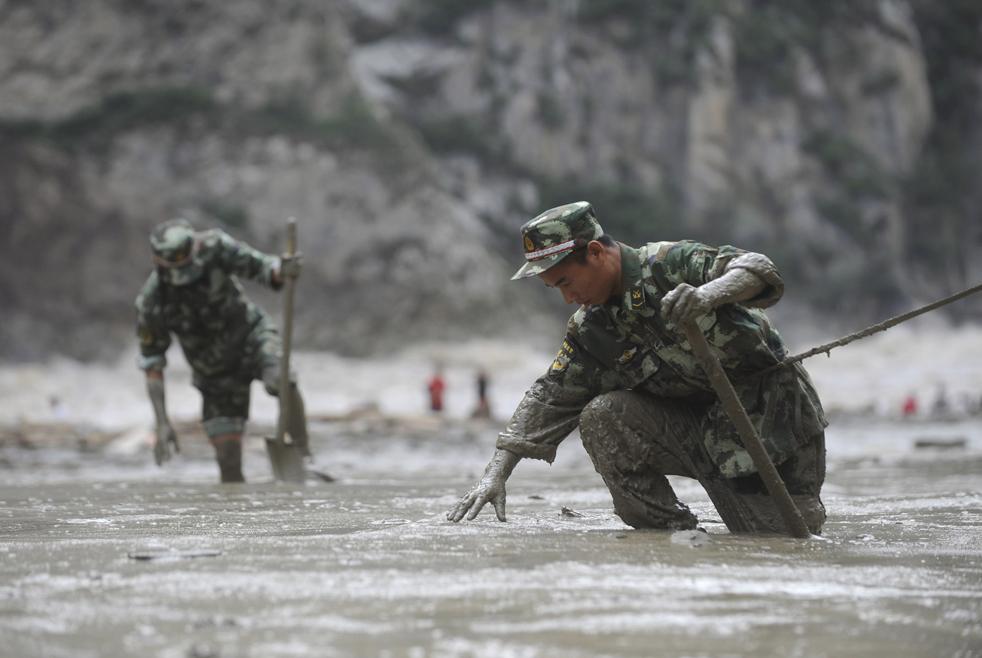 13) На этой фотографии, предоставленной китайским информагентством Синьхуа, спасатели ищут пропавших людей на месте в грязевого оползня в деревне Шелиан уезда Кангдинг в юго-западной китайской провинции Сычуань, в пятницу 24 июля. 53 человек пропали без вести в оползне, вызванном тяжелым ливнем рано утром в Сычуани. 97 человек были также эвакуированы из этой области.(AP/Jiang Hongjing)