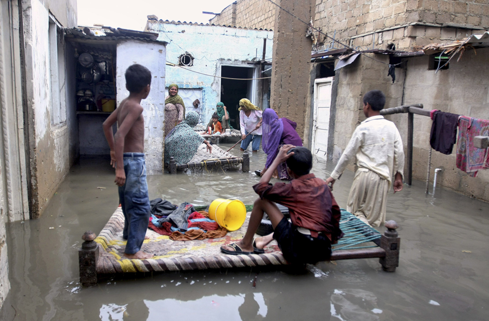 14) Пакистанская семья в доме, который затопило дождевой водой в Карачи, Пакистан, 19 июля. Как сообщают официальные источники, из-за проливных дождей в этом одном из крупнейший городов Пакистана, по меньшей мере 15 человек погибли. Кроме того, в городе было отрезано электричество. (AP/Fareed Khan)