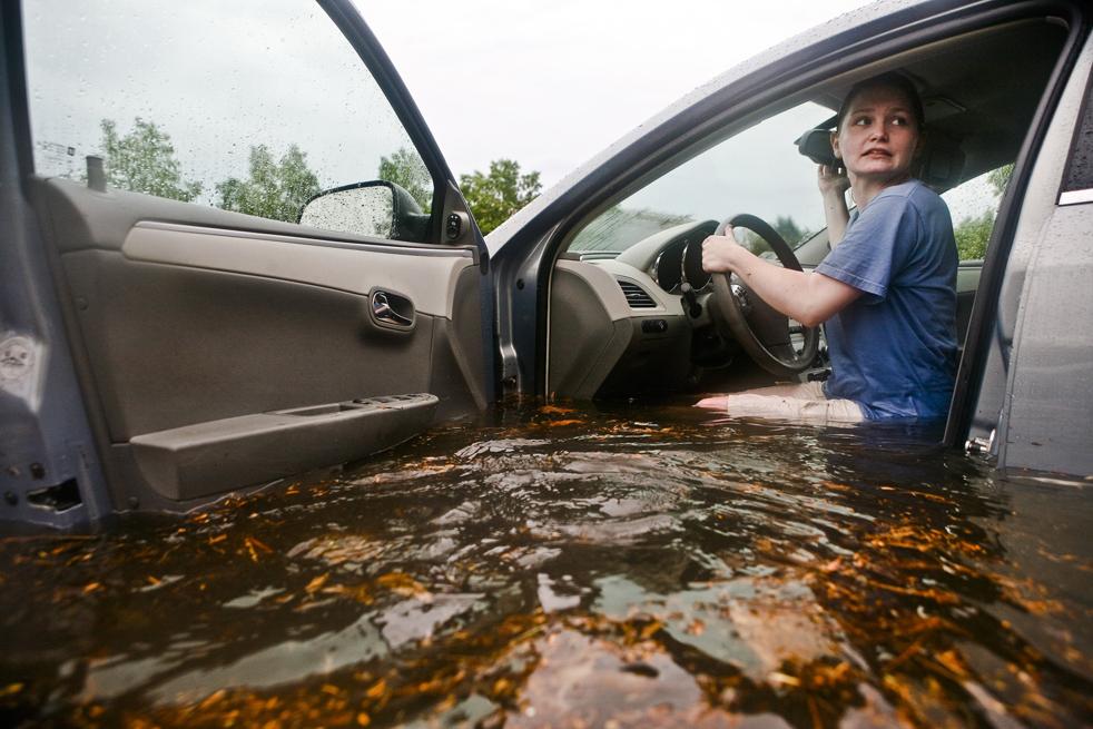 15) Сотрудница «Мистик Аквариум» Эмили МакКейб пытается отогнать свою машину в сухое место на затопленной стоянке у аквариума в Мистик, штат Коннектикут, 1 июля. МакКейб и десятки других сотрудников провели несколько часов, помогая посетителям отгонять свои автомобили, некоторые из которых были наполовину затоплены дождевой водой. (AP/The Day/Tucker Walsh)