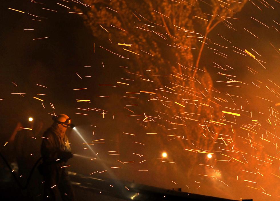 16) Один из членов пожарной бригады тушит пожар в Андорре ночью 23-го июля, около Теруэль. Около 500 человек боролись с раздуваемым ветром лесным пожаром 22 июля  на северо-востоке Испании. В результате пожара четверо пожарных погибли, а двое – были тяжело ранены, сообщил министр обороны Испании Карме Чакона. (AFP/Getty Images/Pedro Armestre)
