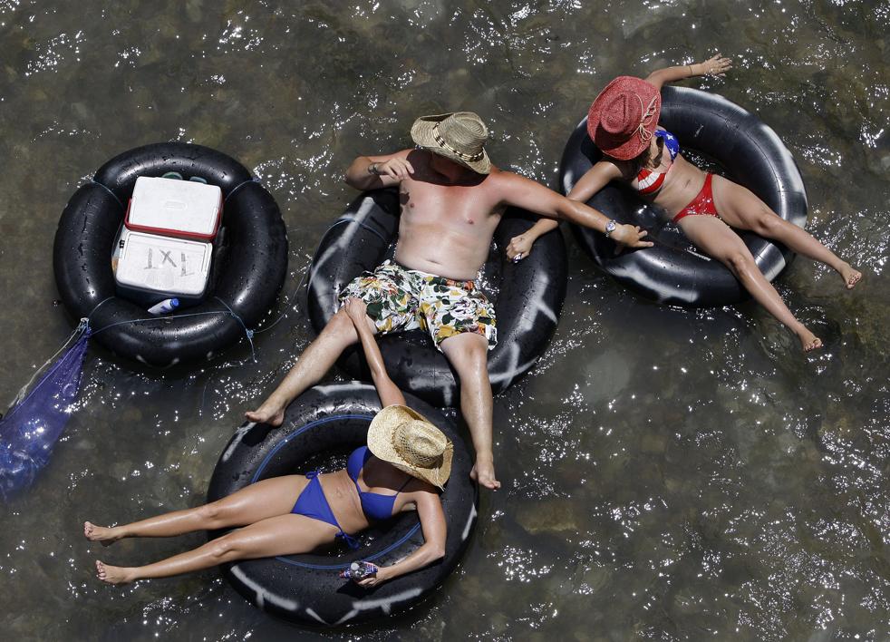 17) Люди плавают на автомобильных камерах в прохладной воде реки Комал в Нью-Браунфелс, штат Техас, в пятницу, 3 июля. В тот день температура доходила до 43ºС. (AP/Eric Gay)