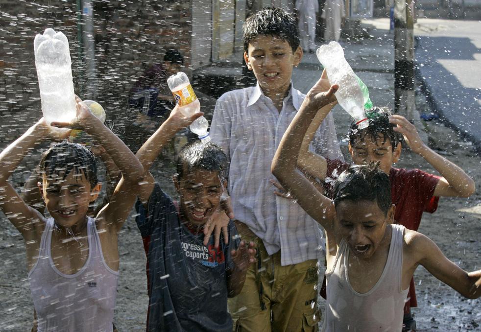 18) Кашмирские дети играют с водой в жаркий летний день в Сринагаре, Индии, в воскресенье, 19 июля. (AP/Мухтар Хан)