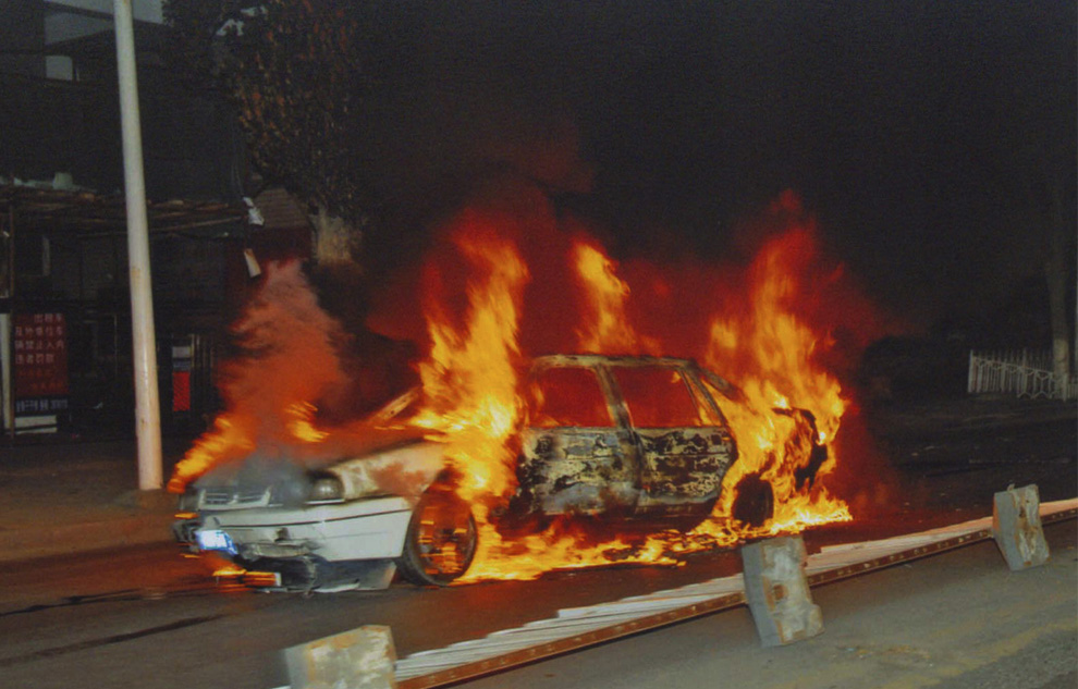 4) На этом снимке сделанном в воскресенье, 5 июля 2009 года и изданном Пресс-службой правительства автономного района Синьцзян, во вторник, 7 июля 2009, виден горящий автомобиль, который лежит на улице после беспорядков в Урумчи. (AP Photo/Xinjiang Government Press Office)