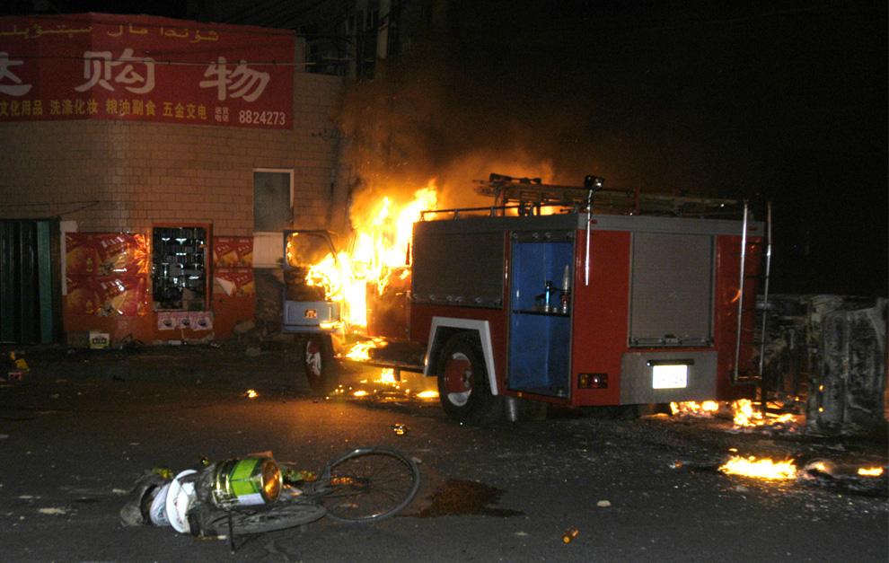"""6) На этой фотографии предоставленном китайским информационным агентством """"Синьхуа"""", пожарная машина горит во время беспорядков в Урумчи, поздно вечером в субботу, 5 июля 2009. (AP Photo/Xinhua, Li Haitao)"""