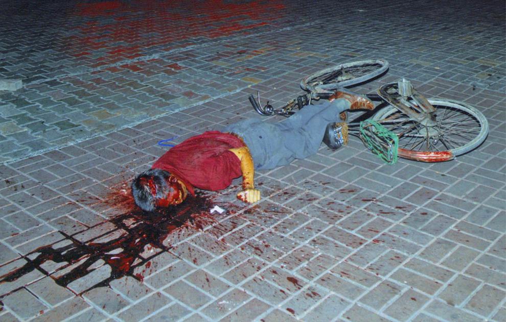 7) Тело жертвы лежит на земле в луже крови. Снимок был сделан 5 июля 2009 года и издано Reuters 7 июля. (REUTERS/Urumqi City Government/Handout)