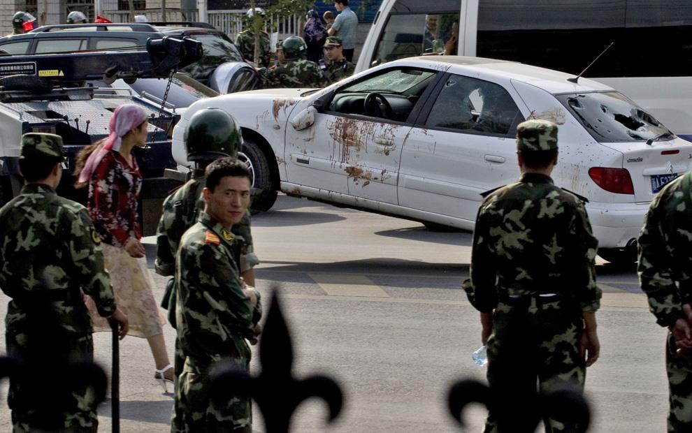 11) Испачканный кровью автомобиль, поврежденный во время протестов, увозят на буксире. Снимок сделан в Урумчи в понедельник, 6 июля 2009. (AP Photo/Ng Han Guan)