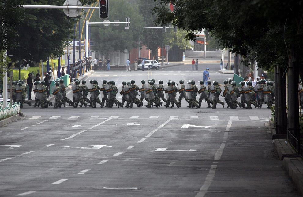 14) Вооруженные солдаты китайской армии идут по главной улице Урумчи, которая ведет к району, занятому этническими уйгурами 8 июля 2009. (REUTERS/David Gray)