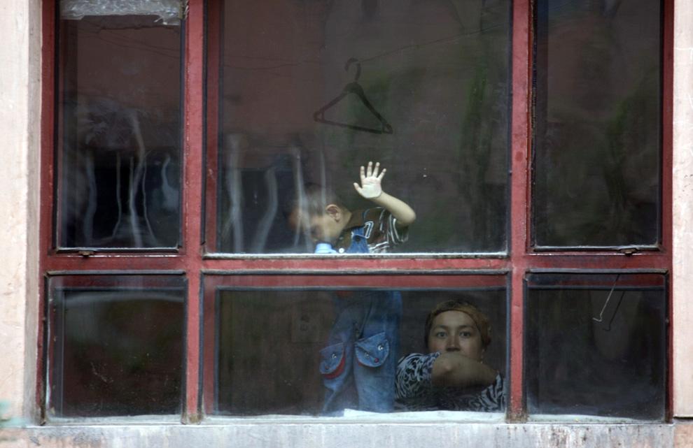 15) Этническая уйгурка смотрит из окна своей квартиры на следующий день после массовых беспорядков в Урумчи в среду, 8 июля 2009. (AP Photo/Ng Han Guan)