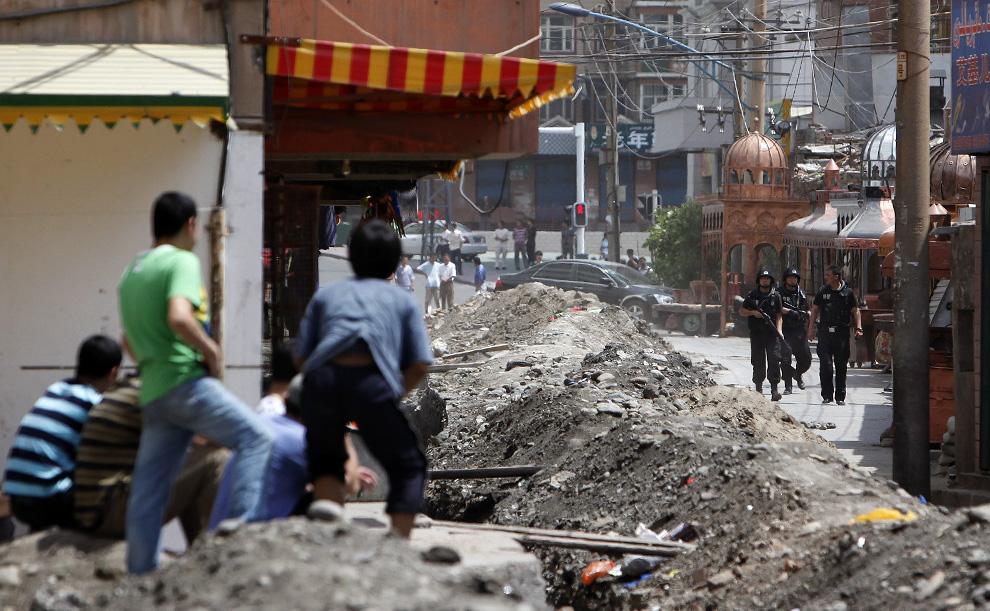 16) Этнические уйгуры смотрят на то, как представители китайских сил безопасности стоят на входе в уйгурский район Урумчи 8 июля 2009. (REUTERS/Nir Elias)