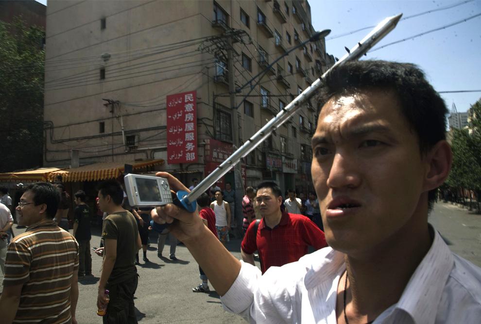 19) Китаец народности хан несет шипастый стальной прут и фотографирует на свой  мобильный телефон, как к нему присоединяется толпа мужчин хань, чтобы напасть на дома уйгуров в Урумчи во вторник, 7 июля 2009. (AP Photo/Ng Han Guan)