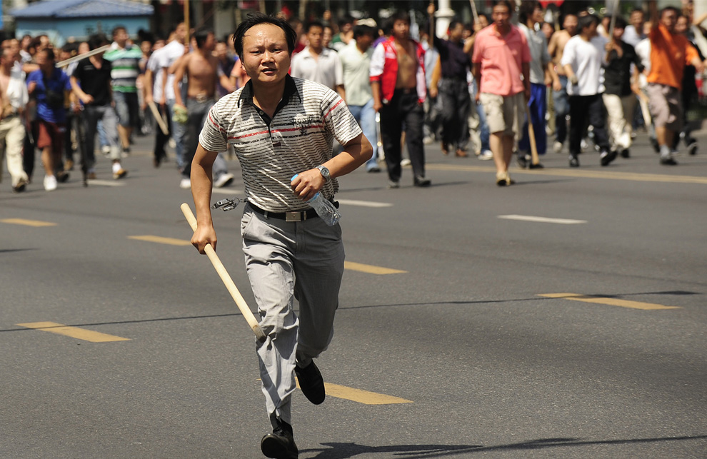 21) Китаец народности хан гонится за фотографом, во время того, как тысячи китайцев вышли на улицы в Урумчи 7 июля 2009. (PETER PARKS/AFP/Getty Images)