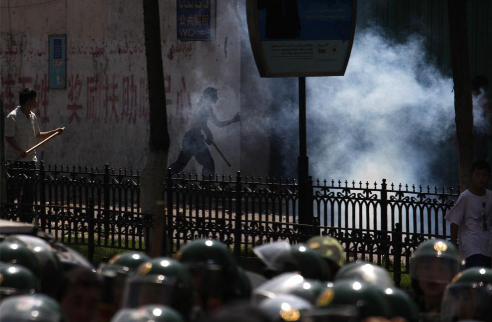22) Китайцы народности хань нападают на уйгурский дом, несмотря на клубы слезоточивого газа, которыми пытается остановить их китайская военизированная полиция. Снимок сделан в Урумчи во вторник, 7 июля 2009. (AP Photo/Ng Han Guan)