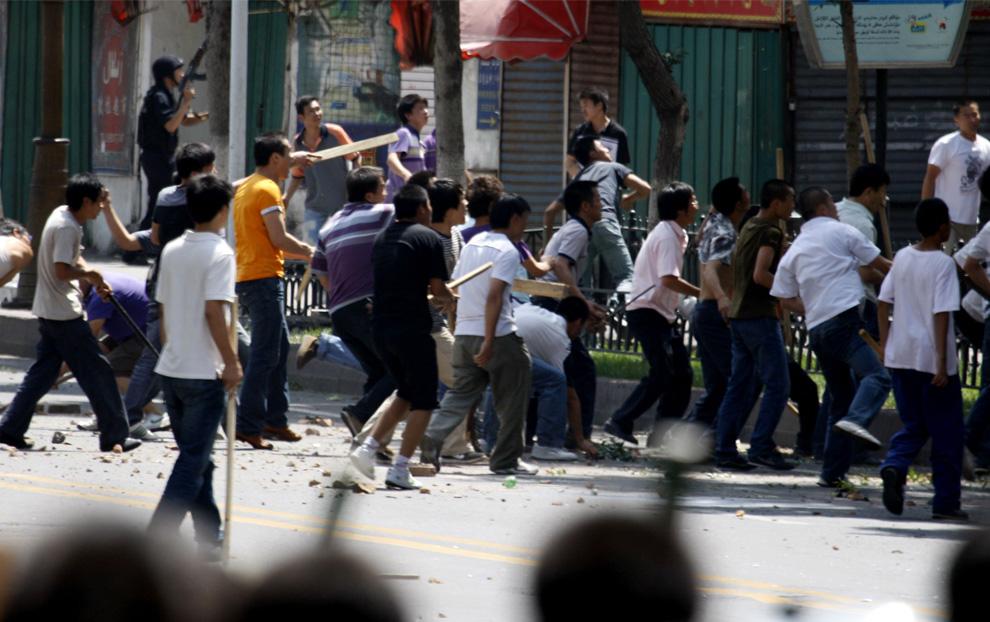 23) Толпа китайцев хань бросают камни в здание, где предположительно скрываются уйгуры. (AP Photo/Ng Han Guan)