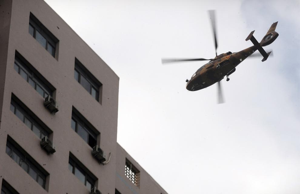 25) Армейский вертолет пролетает над городом Урумчи 8 июля 2009. (PETER PARKS/AFP/Getty Images)