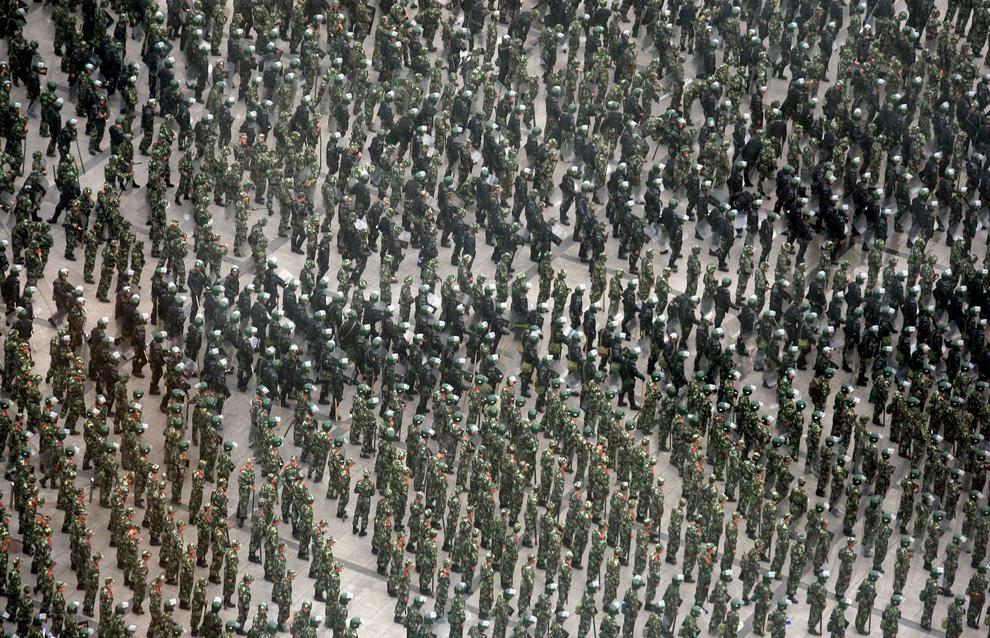 26) Китайские солдаты и полицейские по борьбе с беспорядками стоят вместе на главной площади в городе Урумчи 8 июля 2009. (REUTERS/David Gray)