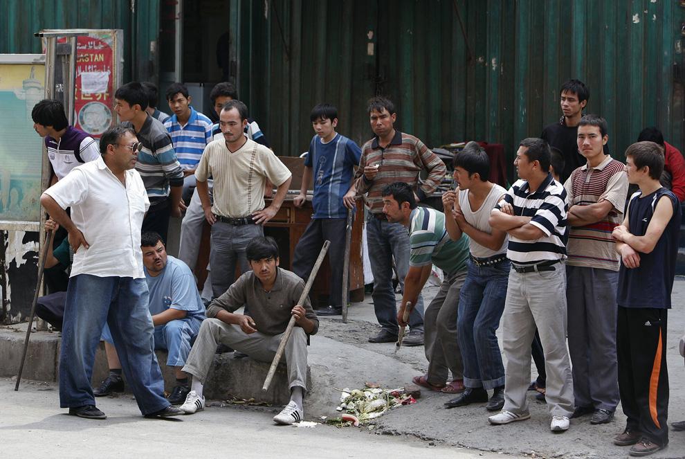 27) Этнические уйгуры с палками ждут у входа в их район, а неподалеку стоят силы безопасности. Снимок сделан в Урумчи 8 июля 2009. (REUTERS/Nir Elias)