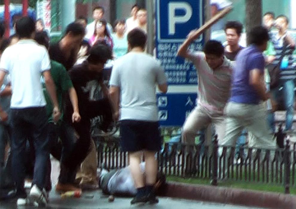 28) На кадре видео, показанного по каналу AFP TV, видно как толпа китайцев хань избивает уйгурца-мусульманина на одной из улиц в Урумчи 8 июля 2009. Группы лиц ханьськой национальности напали на двух уйгуров в городе Урумчи 8 июля, как сообщают журналисты канала AFP, которые были свидетелями этого инциндента. (Sam Beattie/AFP/Getty Images)