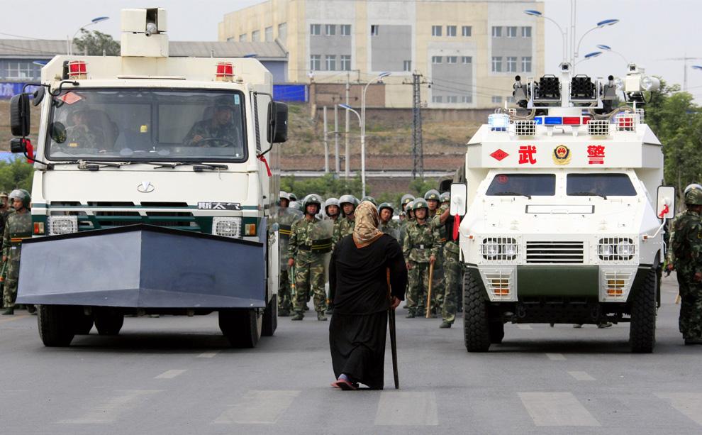 30) Турсун Гюль, местная уйгурка, кричит на солдат, в то время как толпа возмущенных местных жителей противостоит силам безопасности на улице в городе Урумчи 7 июля 2009. (REUTERS/David Gray)