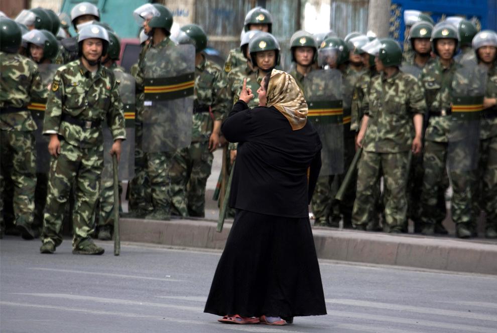 31) Уйгурка Турсун Гюль, стоит напротив китайский военизированных полицейских в Урумчи, Китай во вторник, 7 июля 2009. За Гюль стоит еще толпой уйгуров. Люди кричат солдатам, чтобы те вернули их мужчин - мужа и четырех братьев Гюль арестовали накануне среди других уйгурцев общим числом более 1400. (AP Photo/Ng Han Guan)