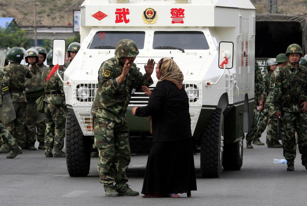 32) Турсун Гюль спорит с полицейским-уйгуром в городе Урумчи 7 июля 2009. (REUTERS/David Gray)