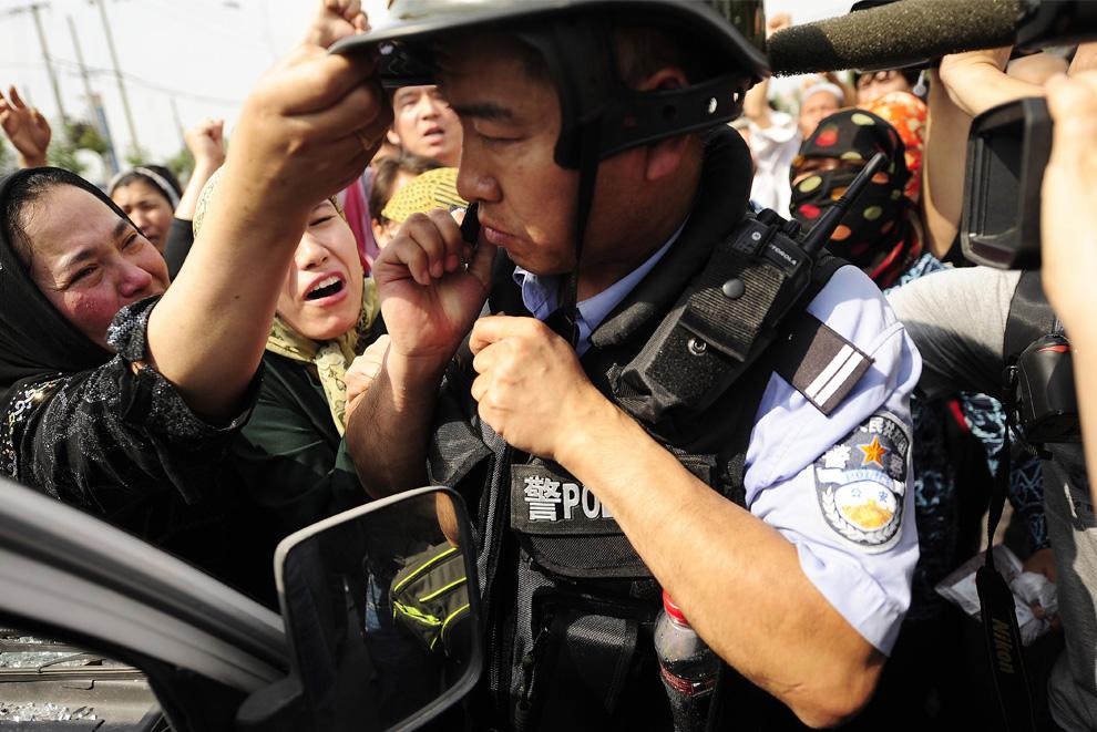 34) Этнические уйгурки пытаются сорвать шлем с полицейского во время беспорядков в Урумчи 7 июля 2009. (PETER PARKS/AFP/Getty Images)