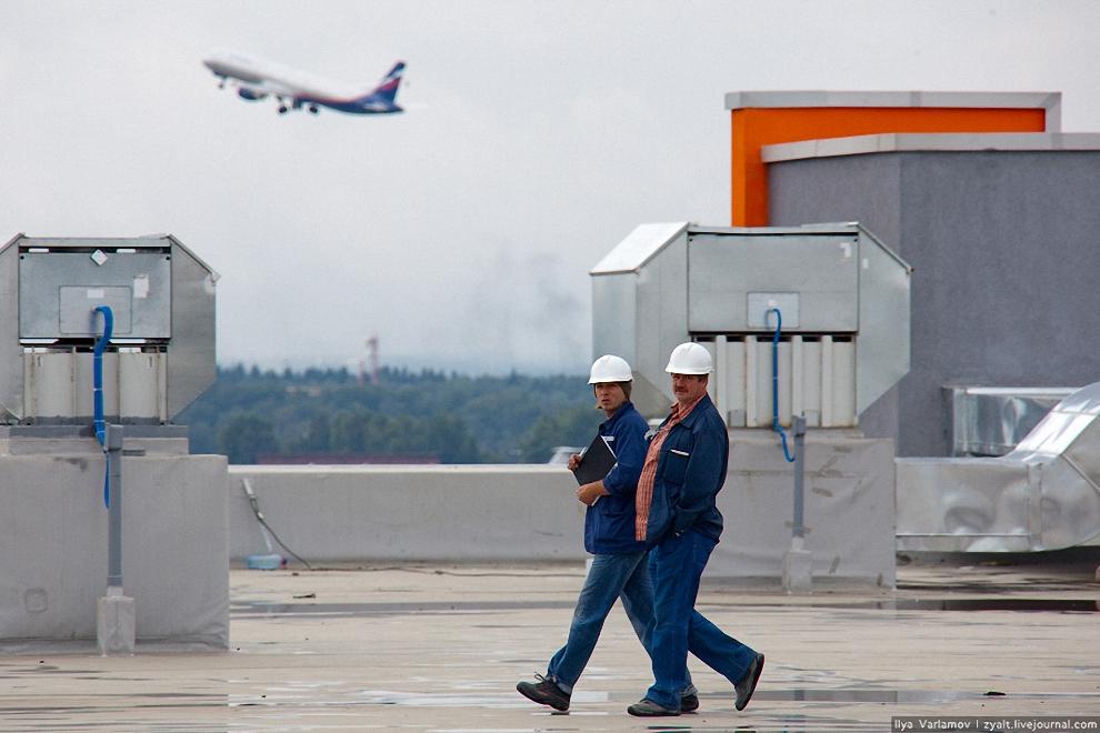 6) Рабочие идут по крыше терминала Е.