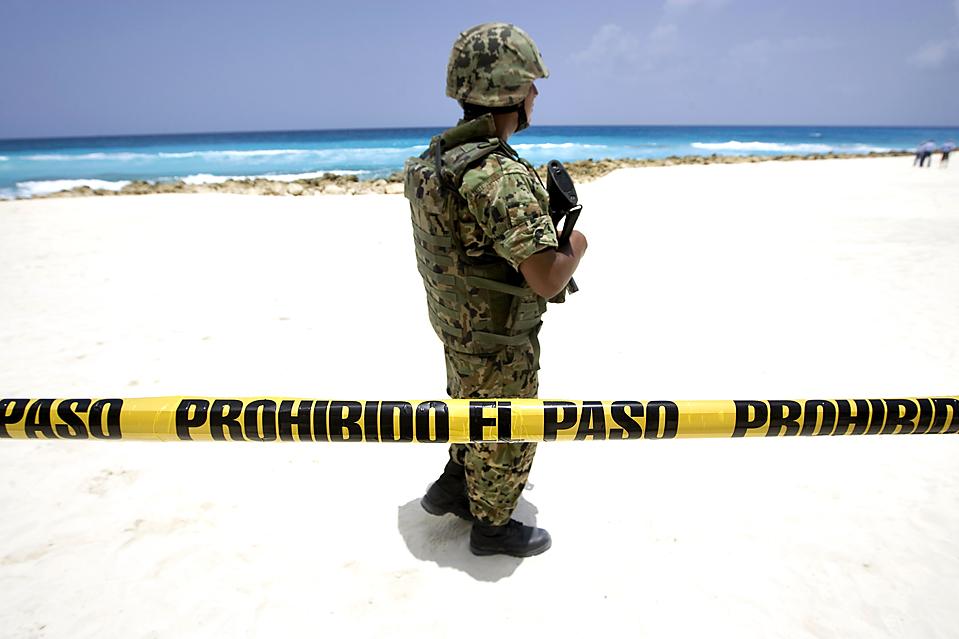 2) Солдат охраняет пляж в городе Канкун, Мексика, среда. Агентство окружающей среды и военно-морские силы  Мексики перекрыли часть пляжа после того, как два отеля были обвинены в незаконном присвоении земли. Пять работников отелей были арестованы по подозрению в незаконной выемке песка. (Gerardo García/Reuters)