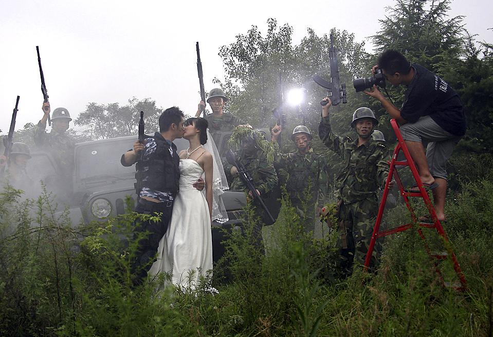 4) Фотограф снимает будущих молодоженов в Нанкине, Китай, среда. Молодожены собираются праздновать свадьбу в военном стиле. В Китае модно фотографироваться перед свадьбой. (Associated Press)