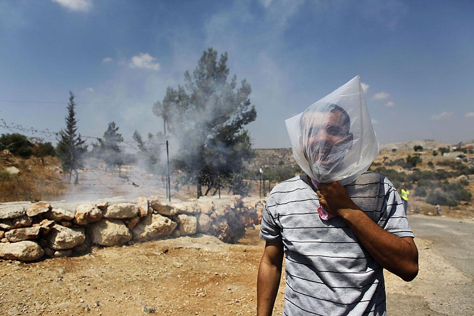 7) Палестинский демонстрант надел на голову целлофановый пакет, так как израильские солдаты выпустили слезоточивый газ во время акции протеста в пятницу в Билине, Западный берег реки Иордан. (Uriel Sinai/Getty Images)