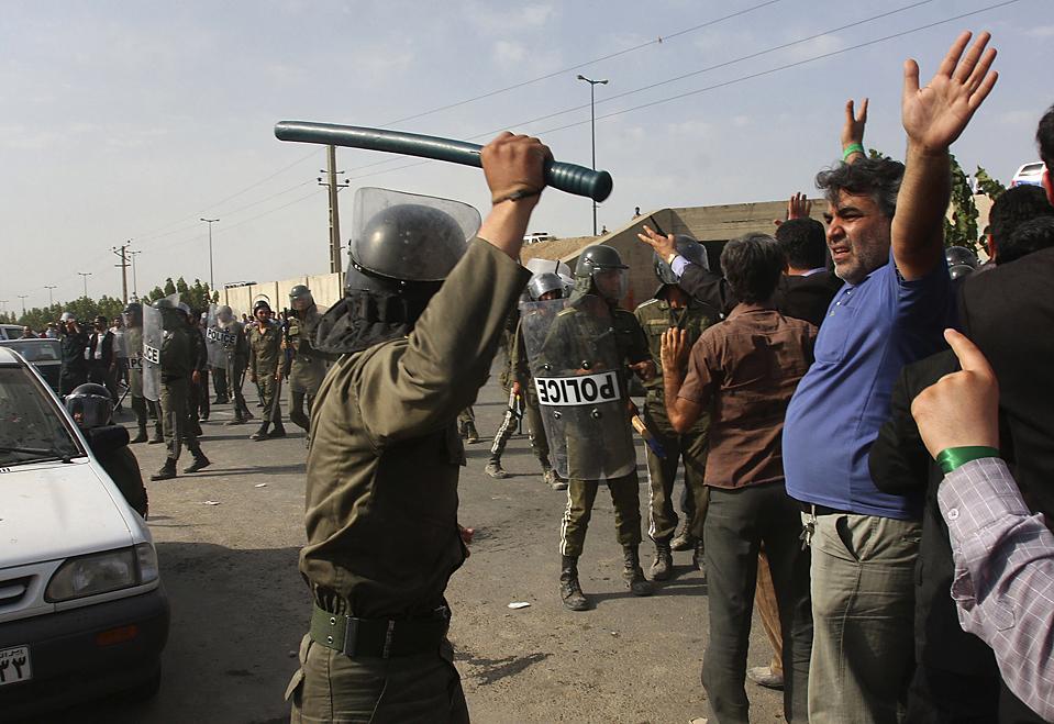 8) Офицер иранской полиции противодействия уличным беспорядкам поднял дубинку, чтобы разогнать протестантов неподалеку от Тегерана, четверг. Протестанты заявляют, что полицейские выпускали слезоточивый газ и избивали их дубинками. Президент Махмуд Ахмадинежад, избранный на второй срок,  заступает на пост на следующей неделе. Из-за определенных ограничений на прессу, которые существуют в Иране, этот снимок был сделан не принадлежащим к ассоциации СМИ фотографом. (Associated Press)