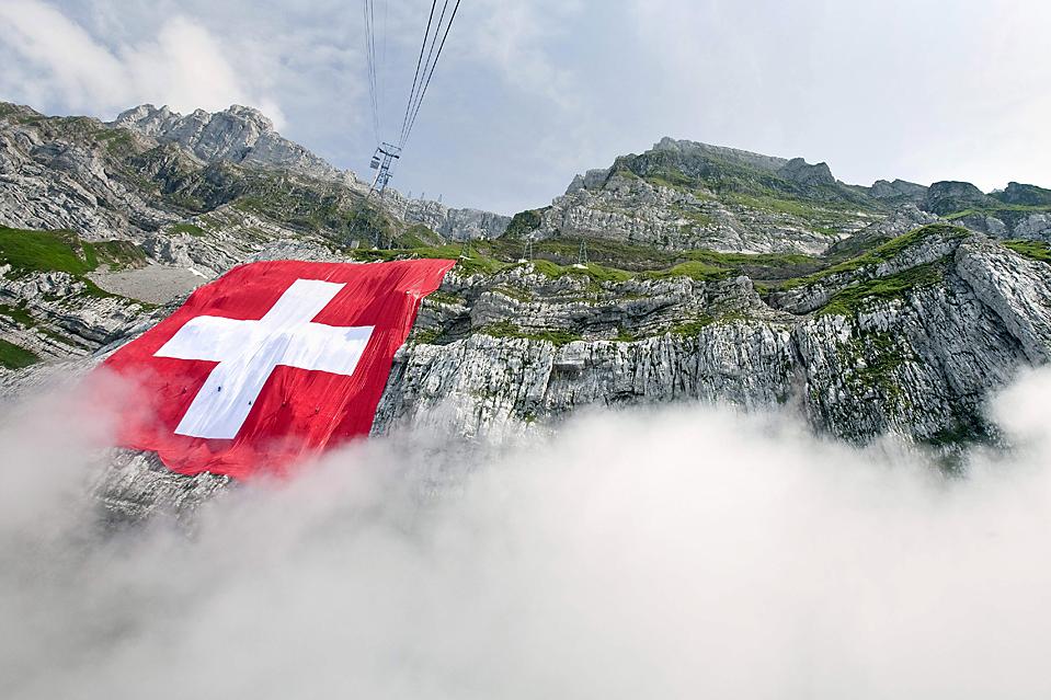 11) Самый большой в мире швейцарский флаг и второй по величине флаг в мире свисает с гор Сантис в Швагальпах, Швейцария, пятница. В субботу в Швейцарии прошел общегосударственный праздник. (Ennio Leanza/Keystone via Associated Press)