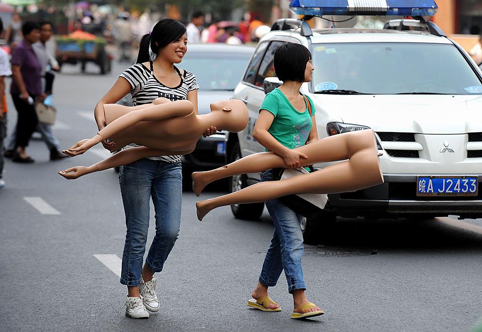13) Девушки несут манекен, направляясь к своему магазину на одной из улиц в Хэфэй, китайская провинция Аньхой, пятница. (Agence France-Presse/Getty Images)