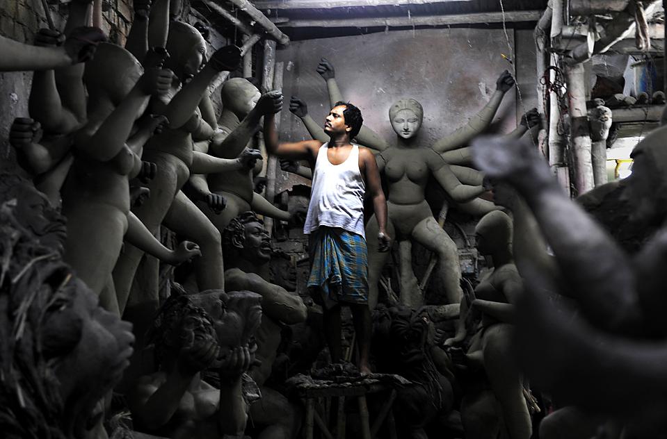 14) Индийский мастер статуэток работает над глиняной статуей богини Дурга в Кумартули, Индия, четверг. Согласно местным отчетам, экспорт статуэток из западно-бенгальского района снизился в период кризиса. (Deshakalyan Chowdhury/Agence France-Presse/Getty Images)
