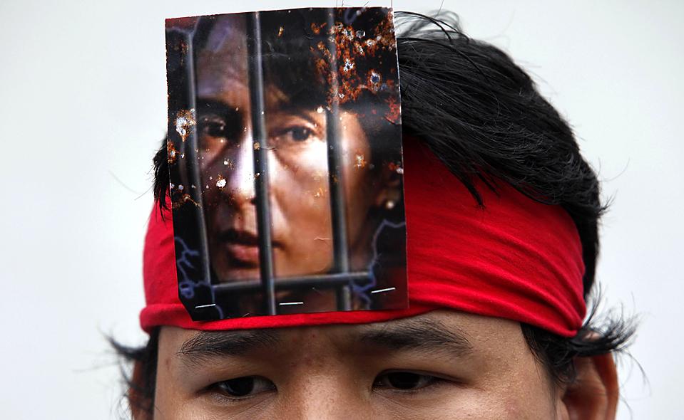15) Жители Мьянмы в Тайланде съехались на митинг перед посольством Мьянмы в Бангкоке в пятницу. Протестанты взывали отпустить продемократического лидера Аун Сан Су Чжи, чью фотографию можно видеть на повязке на этом снимке. Суд Мьянмы отложил вердикт по делу мисс Аун до 11 августа. (Chaiwat Subprasom/Reuters)