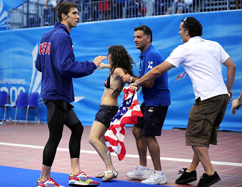 6) Мужчина остановил девушку, которая пыталась обнять Майкла Фелпса после его победы в смешанной эстафете 4×100 метров на Чемпионате мира FINA в Риме в воскресенье. (Alessandro Bianchi/Reuters)