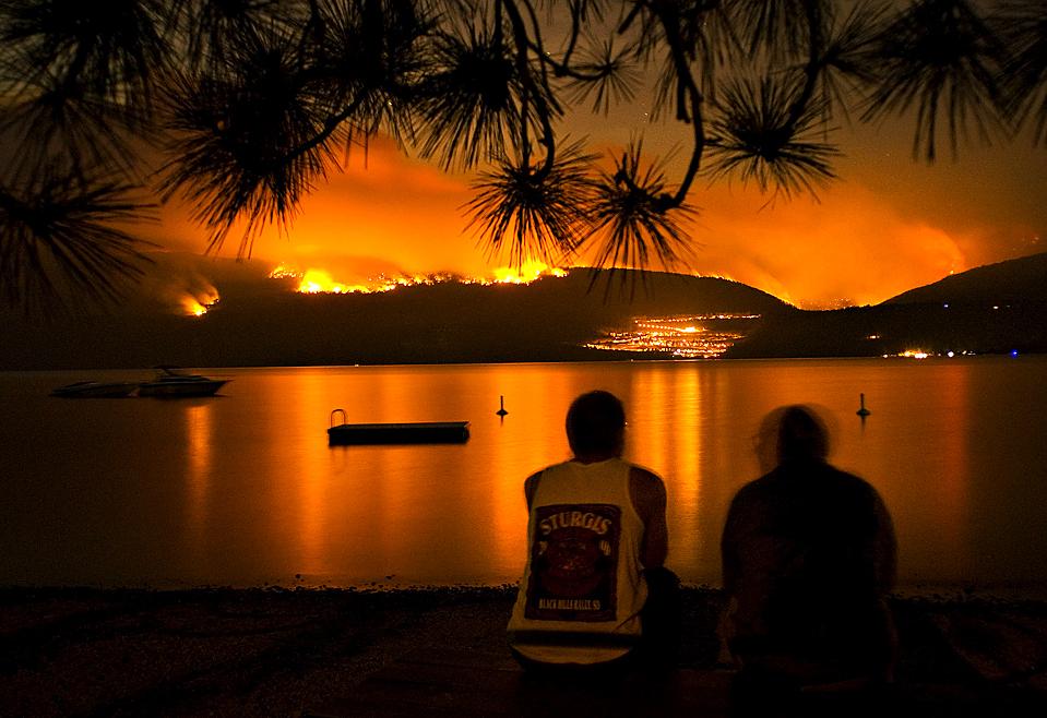 15) Лес Рейн, слева, и Вилле МакХендри наблюдают за пожаром на Горной Терассе утром в воскресенье в Каррс Лендинг, Британская Колумбия, Канада. В воскресенье пожарные гасили около 500-та лесных пожаров, из-за которых пришлось эвакуировать 2700 человек. (Daniel Hayduk/The Canadian Press via Associated Press)